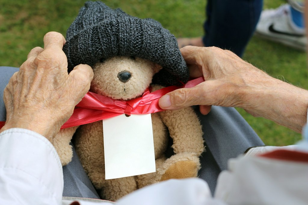 Older person holding a soft toy bear
