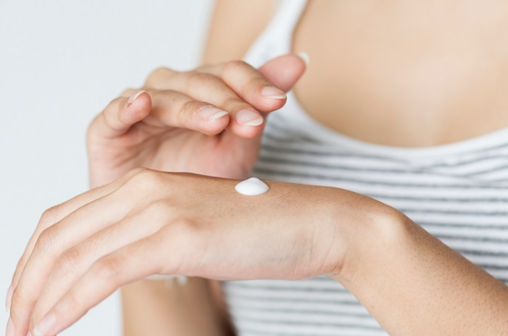 A woman rubbing cream into her hand