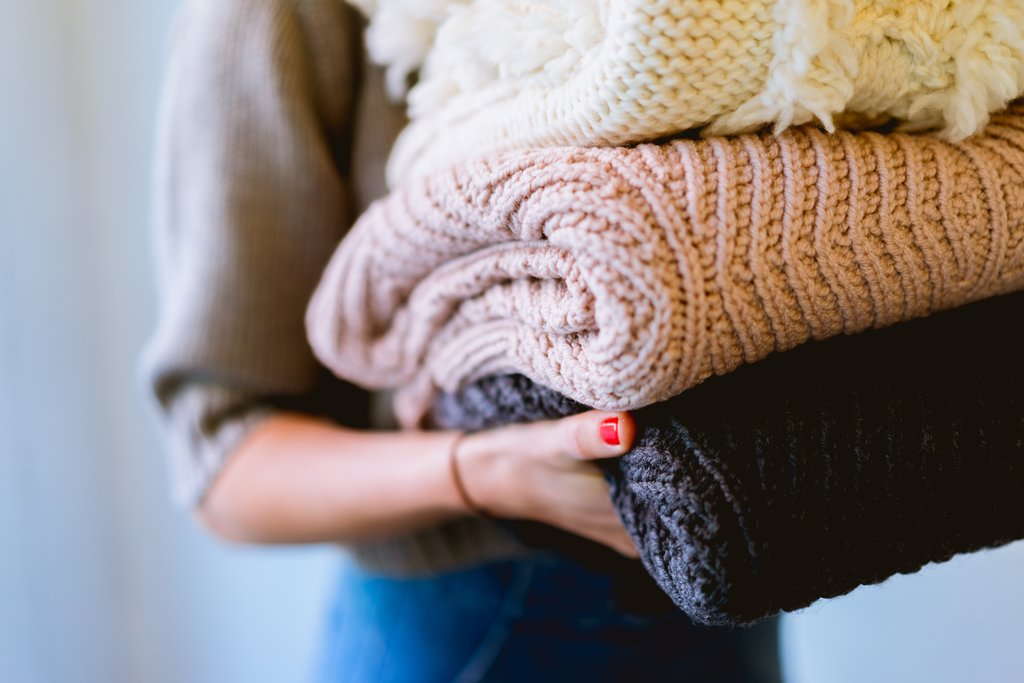 A woman using jumpers to keep warm in winter