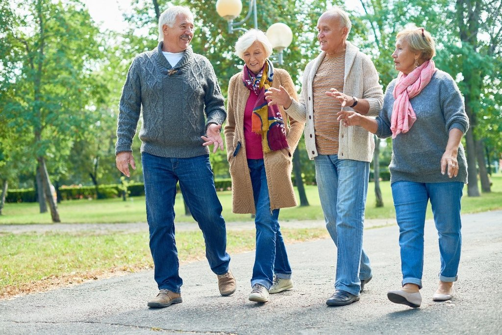 Four older people walking and chatting