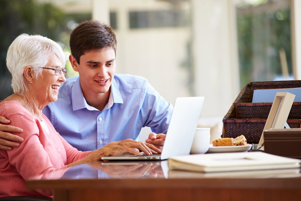 Grandmother and grandson using a laptop
