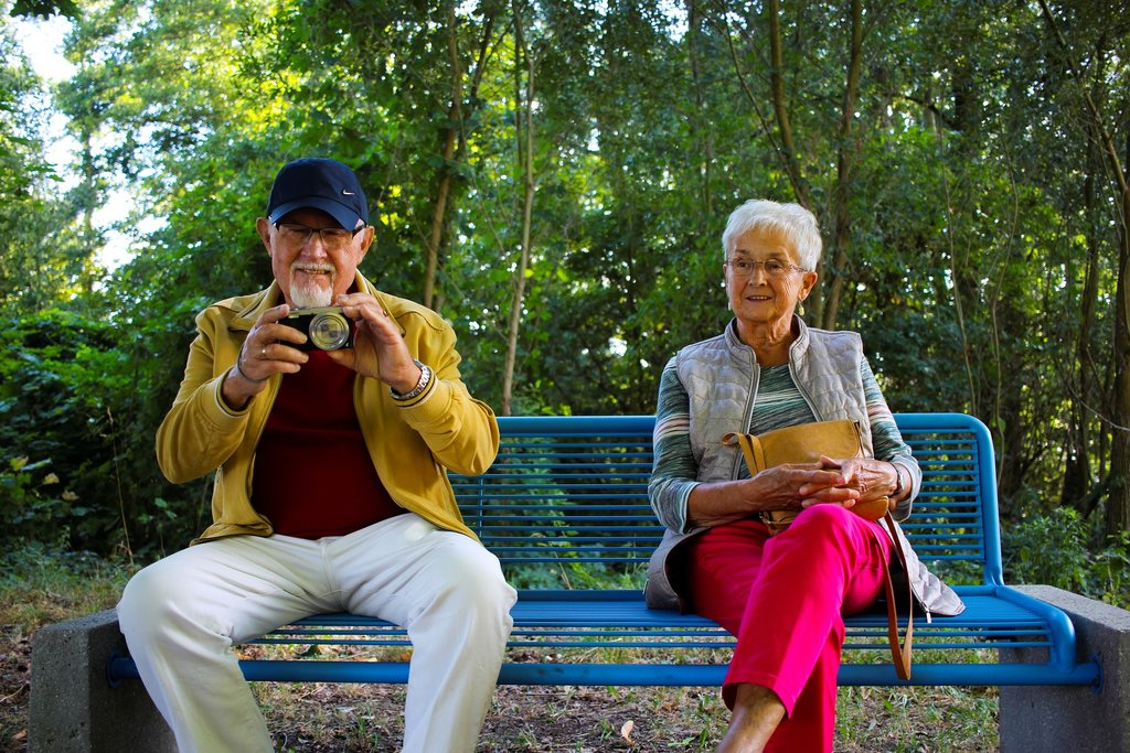 Older couple sat on bench taking a photograph
