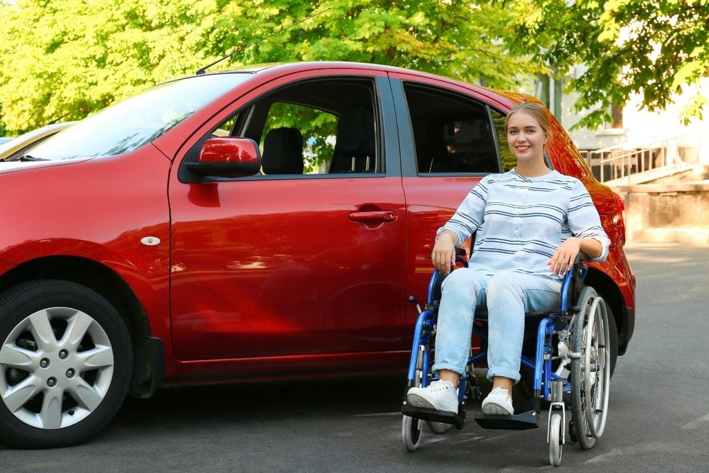 Lady in wheelchair outside red car