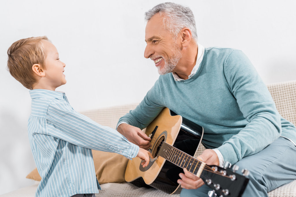 Grandad playing guitar with grandson