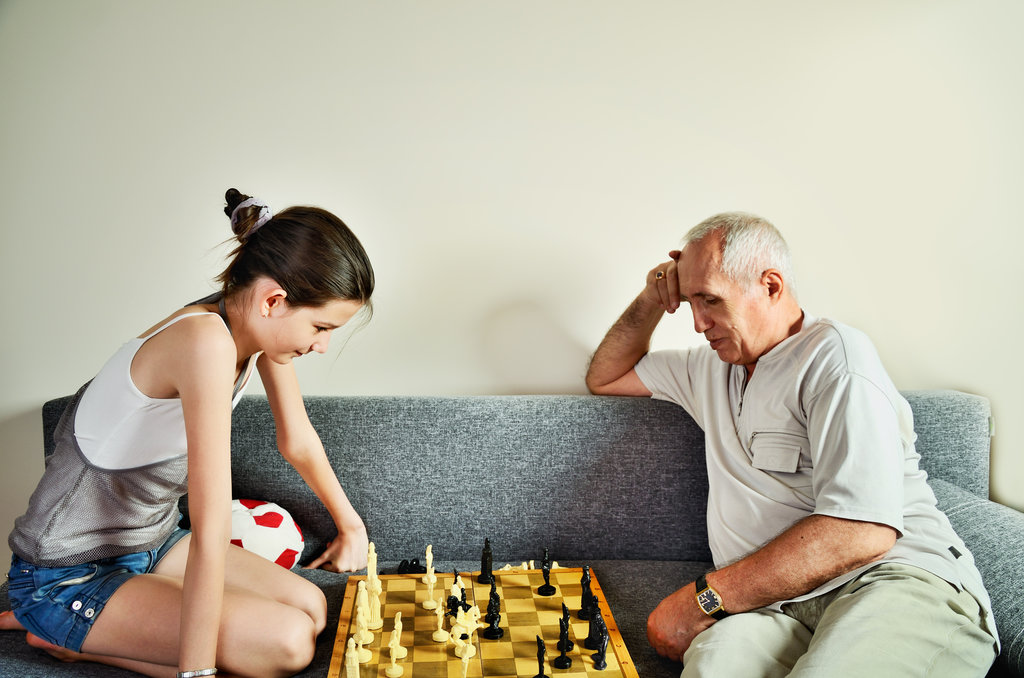 Girl playing chess with grandad