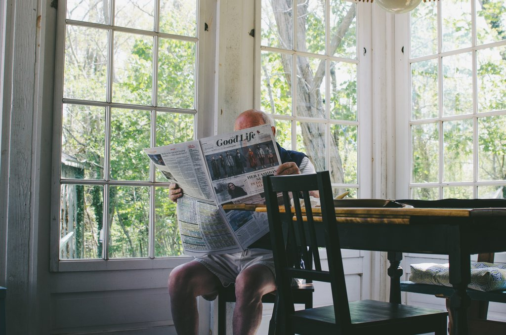 Man sat alone reading the paper