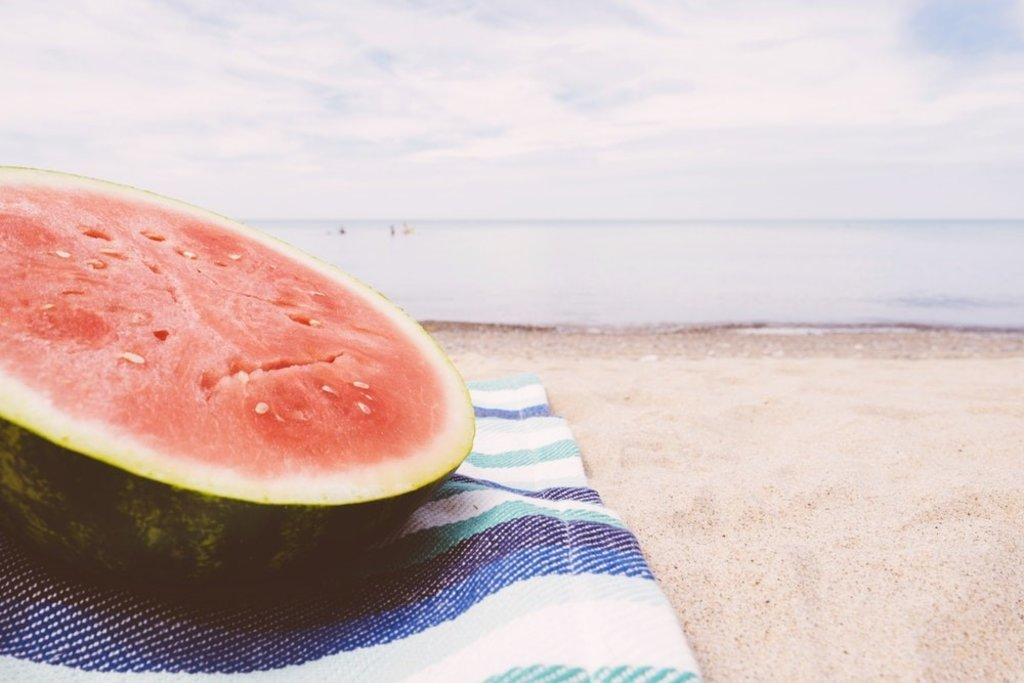 A watermelon on a towel at the beach