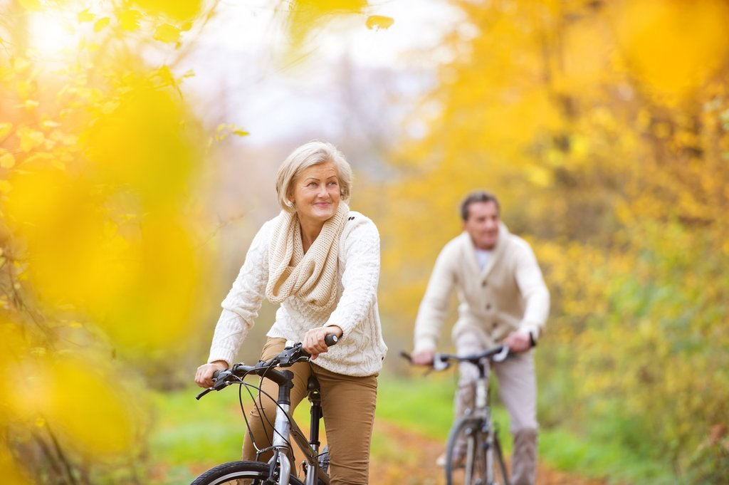 Older couple cycling in Autumn woodland