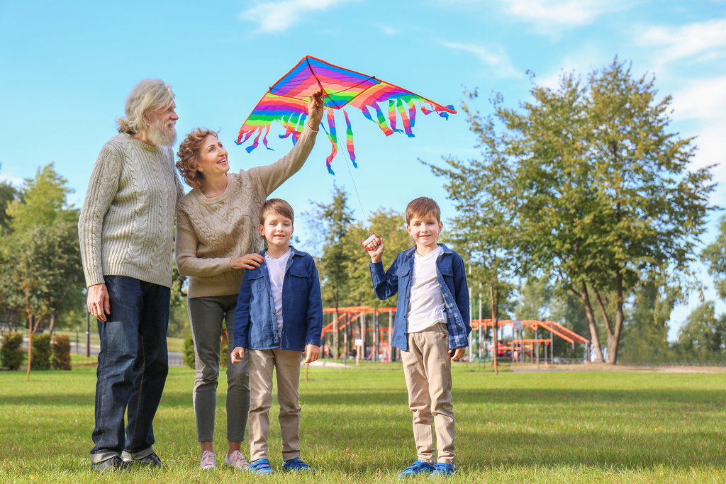 Grandparents flying a kite with their grandchildren