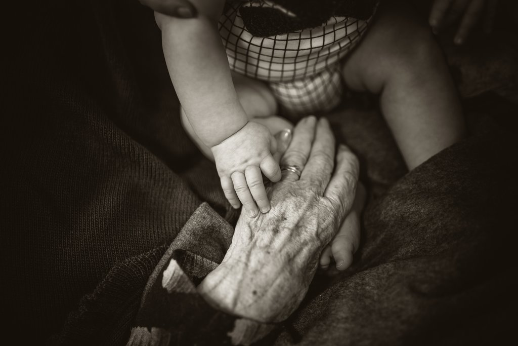 young and old hands together