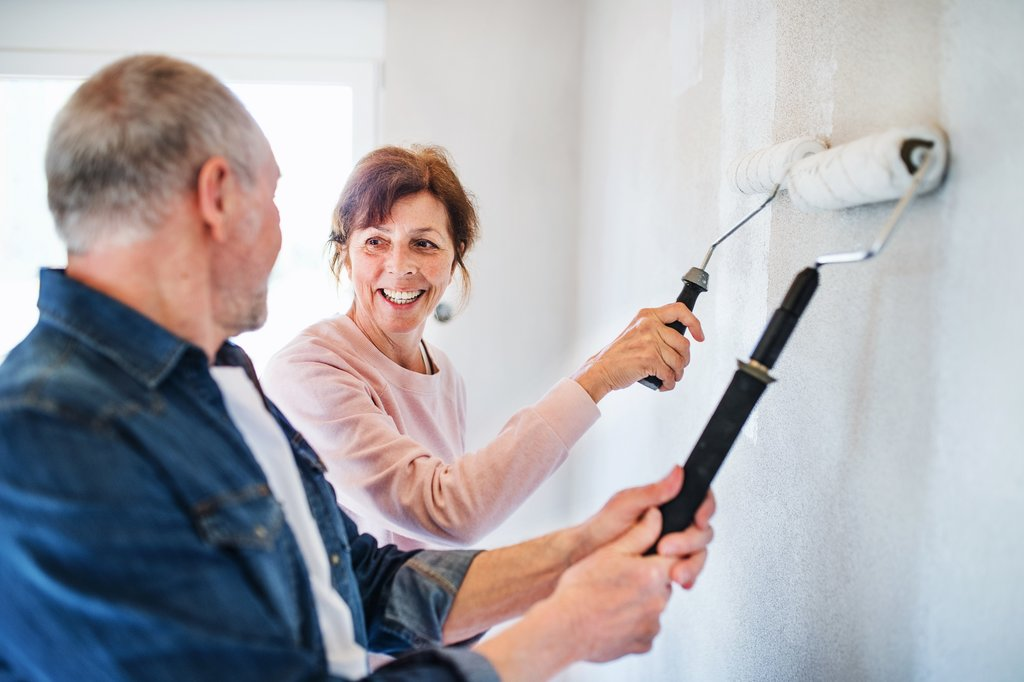 Senior couple painting walls together in house